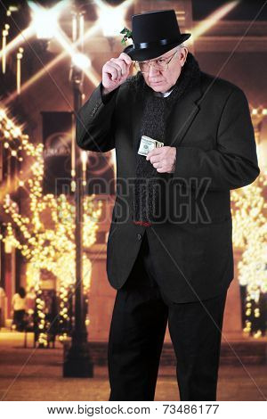 A miserly old man holding onto his top hat while clutching a wad of 100 dollar bills as he walks outside past a Christmas-decorated mall at night.