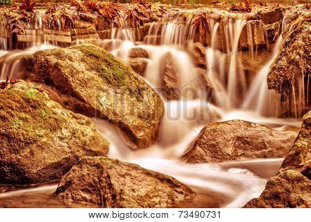 Beautiful waterfall landscape, wild river streaming through stones in mountainous forest, majestic scene, autumn nature concept