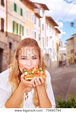 Portrait of cute girl sitting in outdoors restaurant and eating pizza, traditional Italian food, tasting European meal, travel and tourism concept
