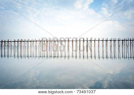 Wooden bridge and reflection on lake water outdoor photography. U Bein, Myanmar