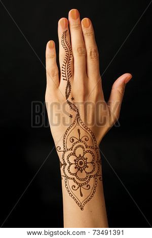hand with mehendi on black background