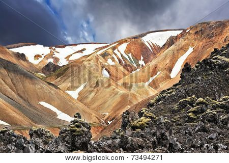 The orange and beige rhyolite mountains with snow in the hollows. National Park Landmannalaugar in Iceland. Pieces of gray and black lava, sometimes covered with green moss.