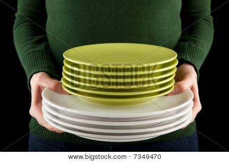 Hands Holding A Pile Of Green And White Dishes