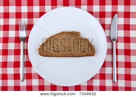 Tablecloth With Fork, Knife And A Slice Of Bread On The Plate