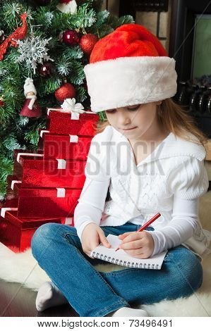Girl In Santa Hat Sits And Writes Letter To Santa
