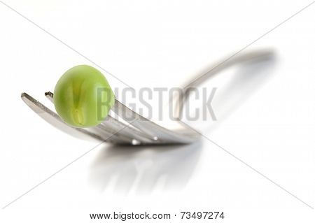 Extreme close-up image of fresh pea and fork