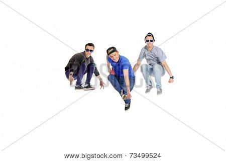 Three professional dancers dancing hip-hop at studio. Isolated over white.