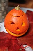 picture of cunning  - little orange oval pumpkin  with cunning face prepare to Halloween holiday - JPG