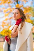 pic of overcoats  - Elegant young woman in a stylish white overcoat standing daydreaming with a bunch of colorful yellow autumn leaves in her hand staring into the distance with a dreamy expression - JPG