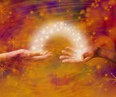 stock photo of mating  - Man and woman both with one hand each palm up with an arc of white light and sparkles joining them on an amber colored energy formation background - JPG