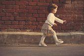 image of girl walking away  - cute little girl walking away near brick wall  - JPG