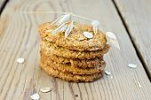 foto of corn stalk  - Stack of oatmeal cookies with cereal and a stalk of oats on the background of wooden boards