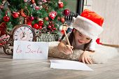 stock photo of letters to santa claus  - Happy girl in Santa hat writes letter to Santa Claus near christmas tree and clock - JPG