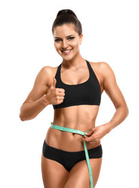 image of measurement  - Athletic slim woman measuring her waist by measure tape after a diet and showing thumb up isolated over white background - JPG