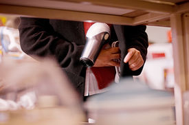 stock photo of shoplifting  - A female in the act of shoplifting or stealing puts an item under her clothes