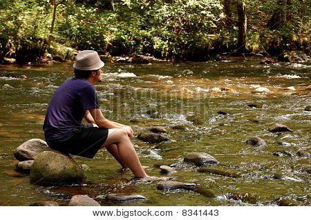 Teen Sitting On River Rocks