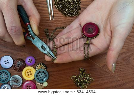 close up of woman's hands making  jewelry