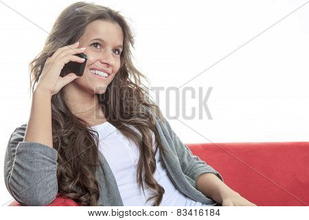 Smiling model sitting on cosy couch in bright living room having a phone call