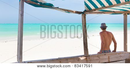 Hipster man with hat on tropical sandy beach.