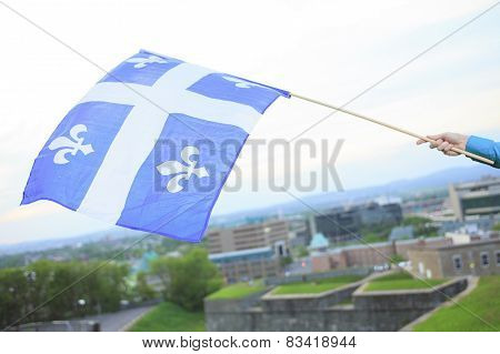 A Quebec flag on the hand of a man