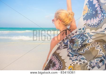 Woman on the beach with colourful scarf.