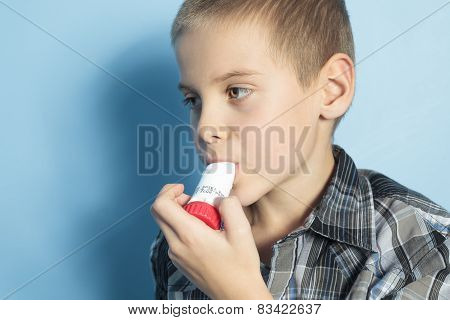 A asthma boy with is inhalator over blue background