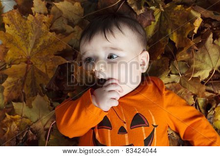 Sweet laughing baby girl playing with a huge pumpkin wearing a knitted pumpkin hat on white backgrou