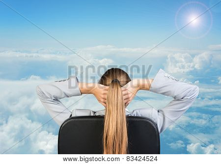 Businesswoman sitting on office chair with hands clasped behind her head