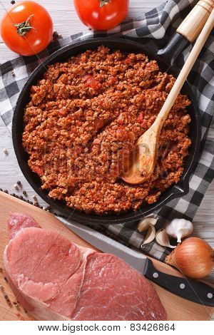 Bolognese Sauce In Pan And Ingredients Vertical Top View Closeup