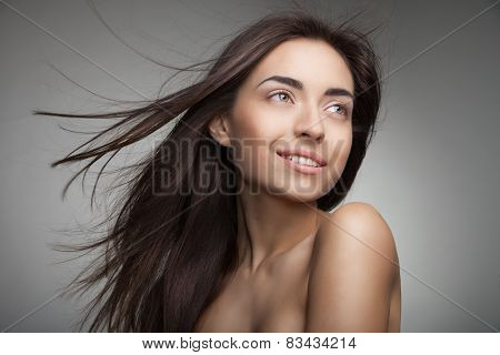 Attractive smiling woman with long hair on grey