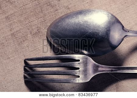 Old Frayed Cutlery On Textile Background