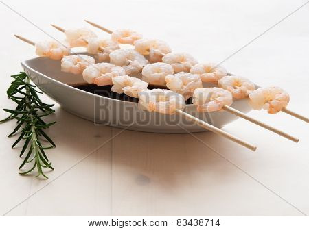 Three skewers with boiled shrimps