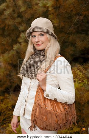 Beautiful autumn woman in yellow park relaxing and smiling