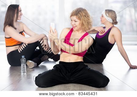 Sporty Woman Using Smartphone On Break In Fitness Class