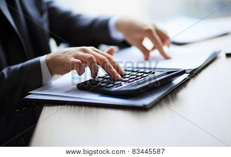 Business people counting on calculator sitting at the table.