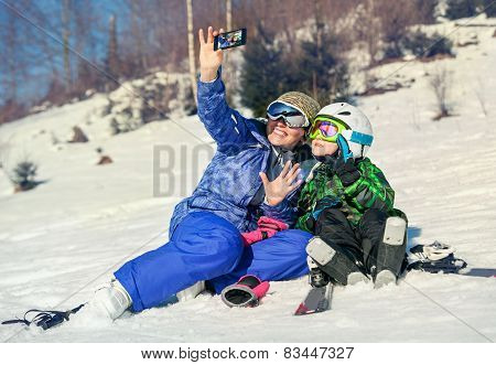 Mother and little son selfie on the ski slope resort