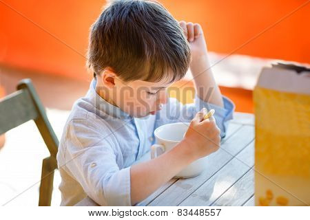 Cute little boy eating dairy breakfast