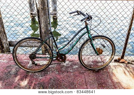 Old Rotten Bike At A Rusty Fence
