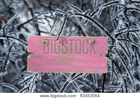 Blank pink wooden sign hanging on ice covered tree branches