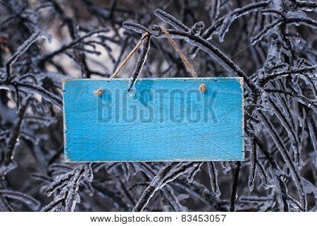 Blank antique wooden sign hanging on ice covered tree branches