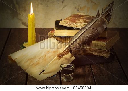 Old books, candle and feather with inks
