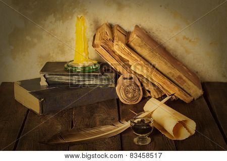 Old books, candle and feather amulet with ink