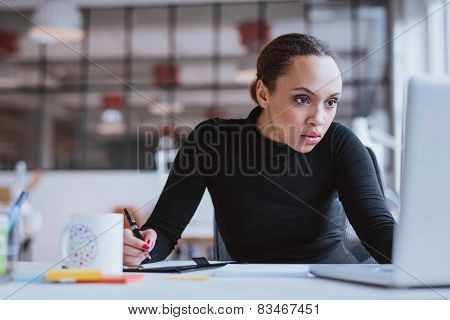 Busy Young Woman Working At Her Desk