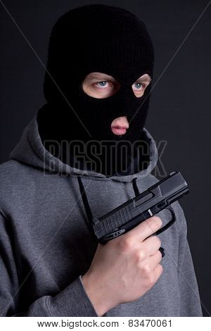 Man Criminal In Black Mask With Gun Over Grey