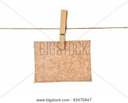 Sheet Of Kraft Paper Hanging On A Rope With Clothespin On A White Background