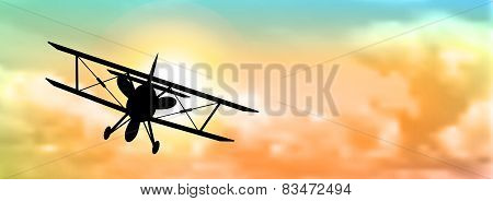 Silhouette Of Biplane With Clouds