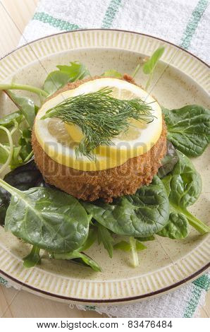 Fish Cake With Lemon Slice On Green Salad