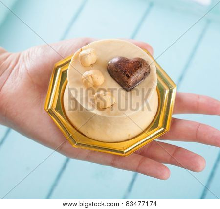 Small Cake With Hazelnuts In Female Hand.