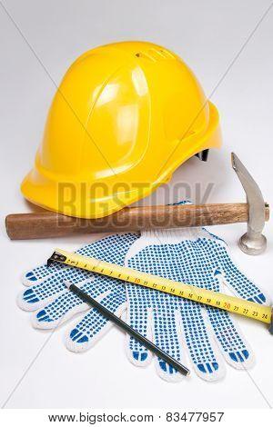 Builder's Tools - Helmet, Work Gloves, Hammer, Pen And Measure Tape Over White