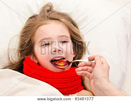 Sick Little Girl In Bed Taking Medicine